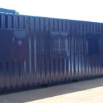 Exterior rear of converted container for motor sports including pedestrian door
