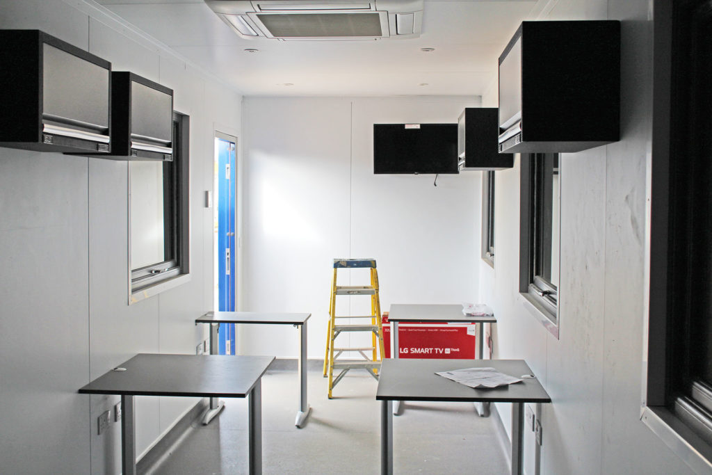 Interior of container office with TV and aircon units